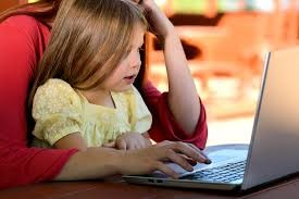 Parent and child sitting together for online school sessions.